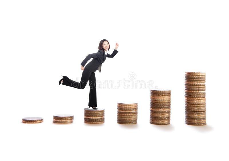 Mulher de negócio nova que funciona em escadas do dinheiro fotografia de stock