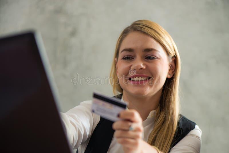 Mulher de negócio nova que guarda o cartão de crédito e que usa o laptop Conceito em linha da compra imagens do estilo do efeito  foto de stock