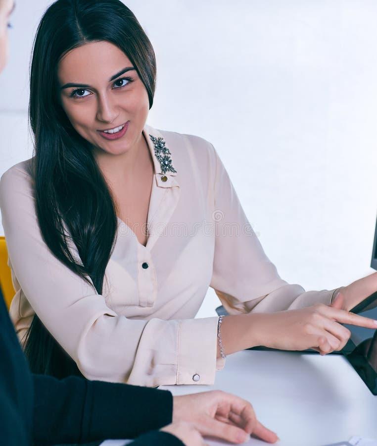 Mulher de negócio nova que guarda a tabuleta e que discute determinado caso com seu colega fotografia de stock royalty free