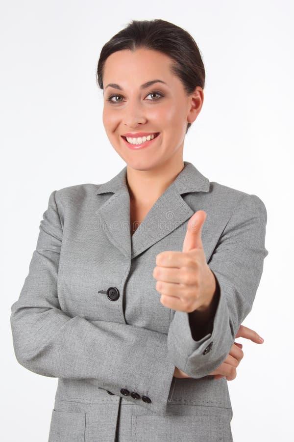 Mulher de negócio nova que mostra o sinal do sucesso fotografia de stock royalty free