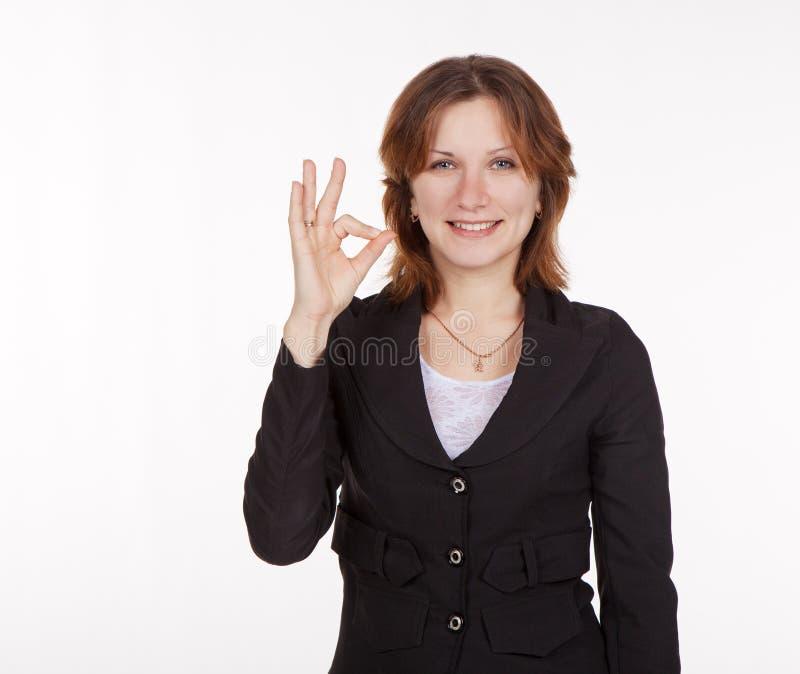 A mulher de negócio nova que mostra todo um gesto é boa