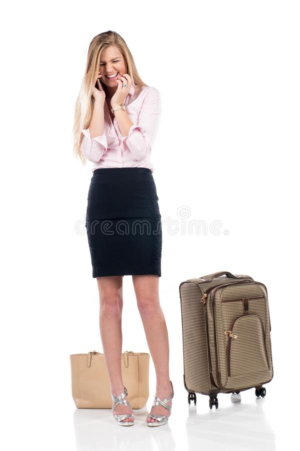 Mulher de negócio nova que ri no telefone ao estar ao lado de suas mala de viagem e bolsa Isolado no branco foto de stock
