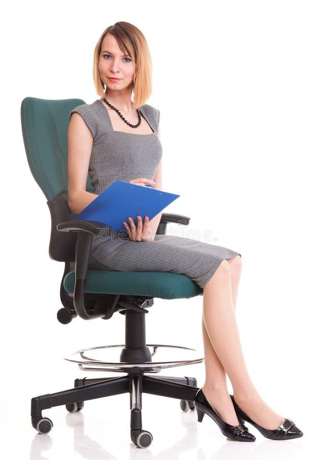 Mulher de negócio nova que senta-se com sua prancheta isolada foto de stock