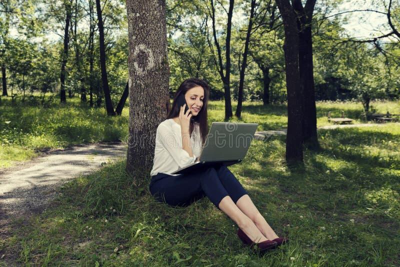 Mulher de negócio nova que senta-se em uma terra e que trabalha em seu portátil e que fala no telefone em um parque público imagens de stock