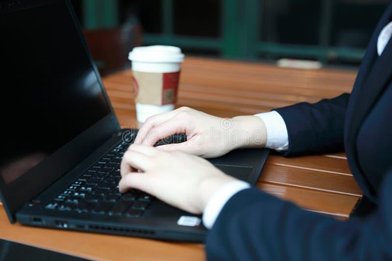 Mulher de negócio nova que senta-se na cafetaria na tabela de madeira, café bebendo Na tabela é o portátil fotos de stock