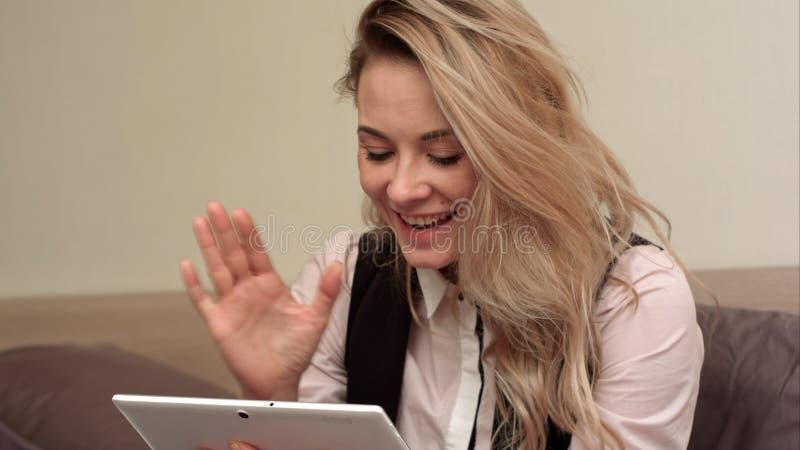 Mulher de negócio nova que senta-se na cama em um quarto do hotel que tem um bate-papo video através da tabuleta, discutindo prob foto de stock royalty free