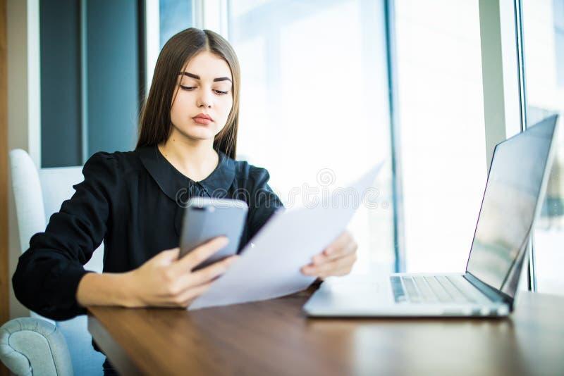 Mulher de negócio nova que senta-se na tabela A mulher assina originais, gráfico da posse e smartphone da utilização Na tabela é  fotografia de stock