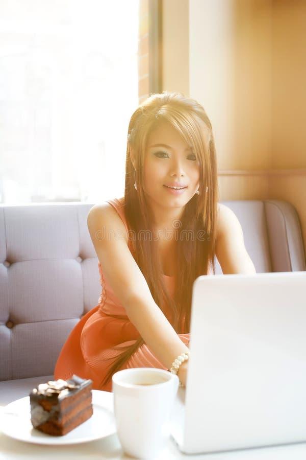 Mulher de negócio nova que senta-se no café com seu portátil foto de stock