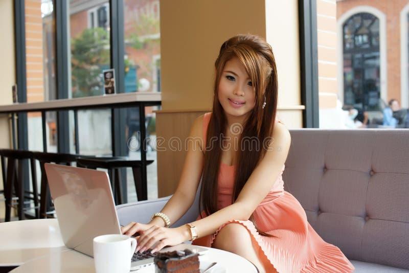 Mulher de negócio nova que senta-se no café com seu portátil fotografia de stock