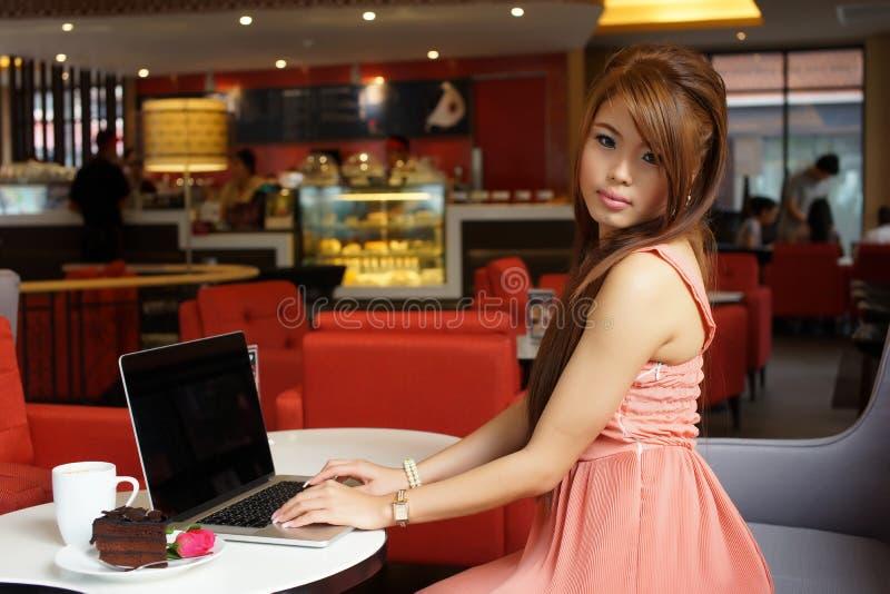 Mulher de negócio nova que senta-se no café com seu portátil fotos de stock