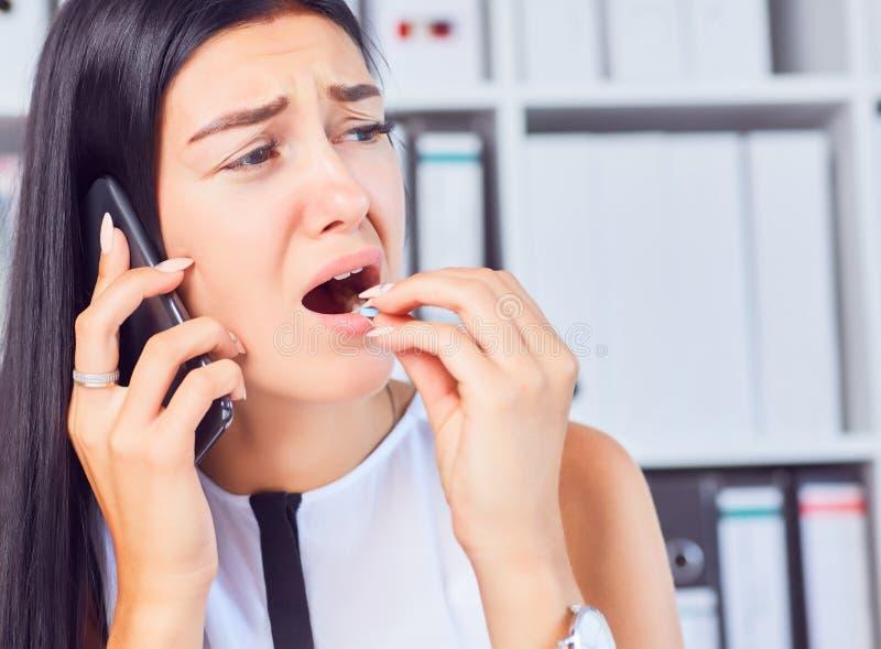 Mulher de negócio nova que toma a medicina em uma situação fatigante no local de trabalho A mulher consulta no telefone com seu d imagens de stock royalty free