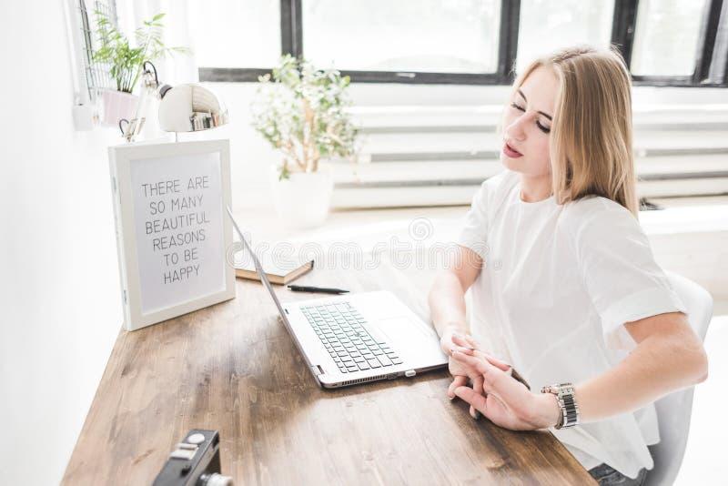 Mulher de negócio nova que trabalha em casa atrás de um portátil e que estica suas mãos Espaço de trabalho escandinavo criativo d imagens de stock royalty free
