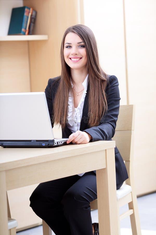 Mulher de negócio nova que usa o portátil imagem de stock