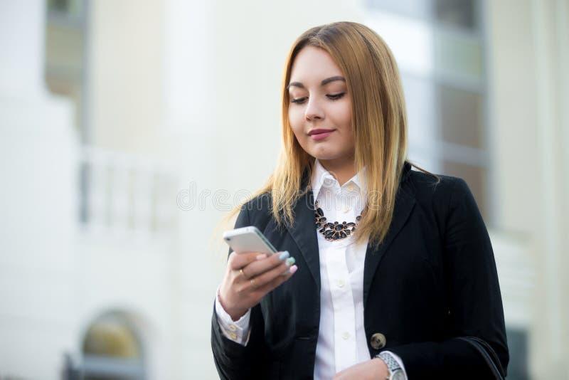 Mulher de negócio nova que usa o smartphone fotografia de stock royalty free