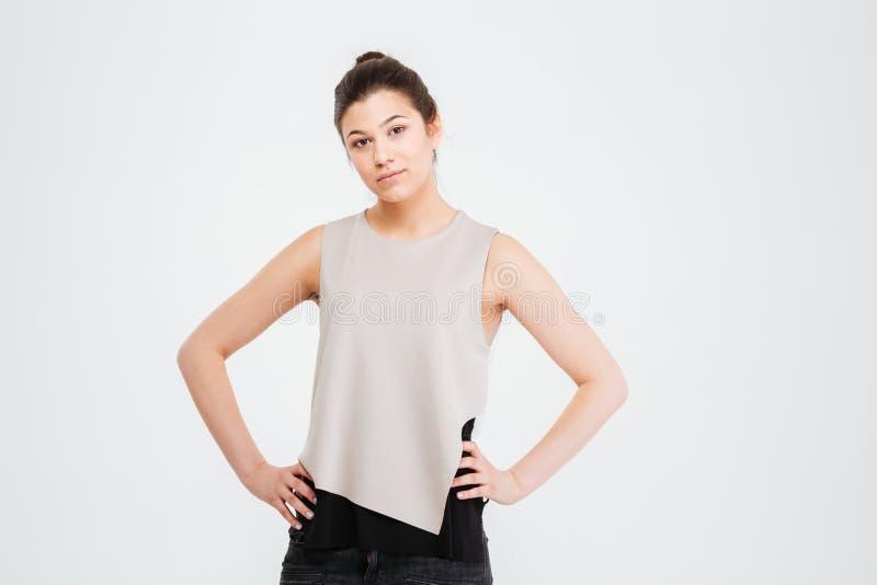 Mulher de negócio nova séria segura que está com mãos na cintura foto de stock royalty free