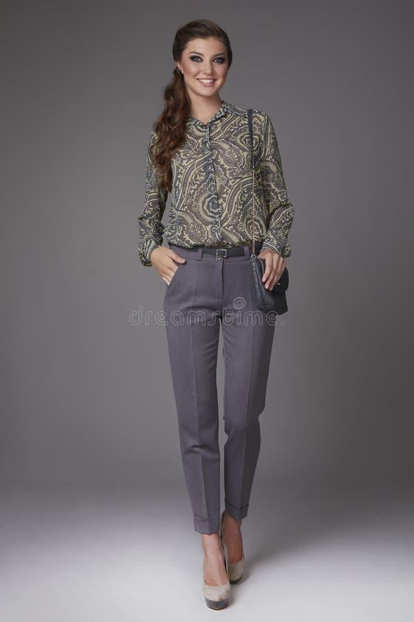 A mulher de negócio nova 'sexy' bonita com composição da noite vestiu-se na blusa apertada do calça e a de seda com as luvas e al imagem de stock royalty free