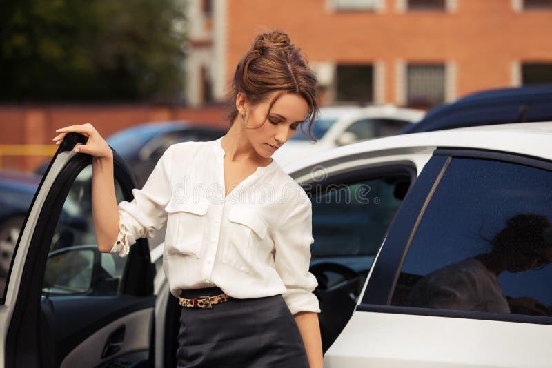 Mulher de negócio nova triste da forma que está ao lado de seu carro imagens de stock royalty free
