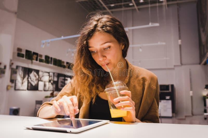A mulher de negócio nova usa uma tabuleta e bebe o suco de laranja recentemente espremido de uma palha em um café foto de stock