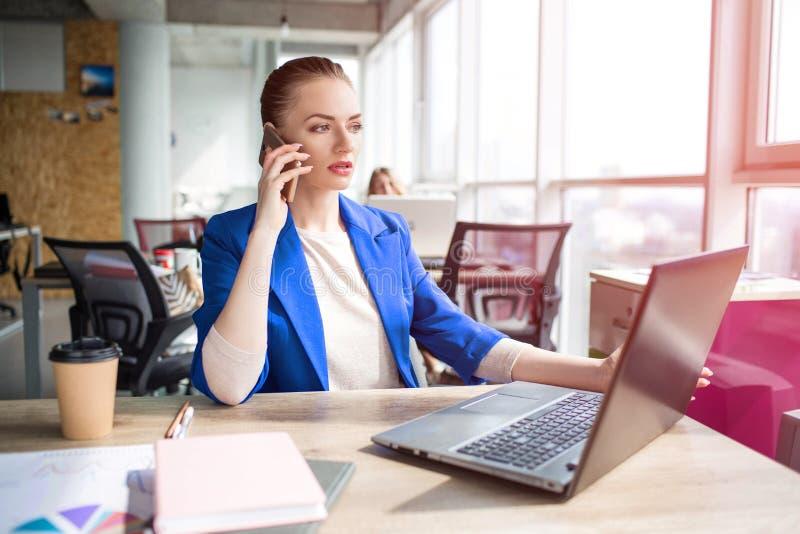 A mulher de negócio ocupada e séria está sentando-se na tabela no escritório e está olhando-se ao portátil Está trabalhando També imagem de stock royalty free