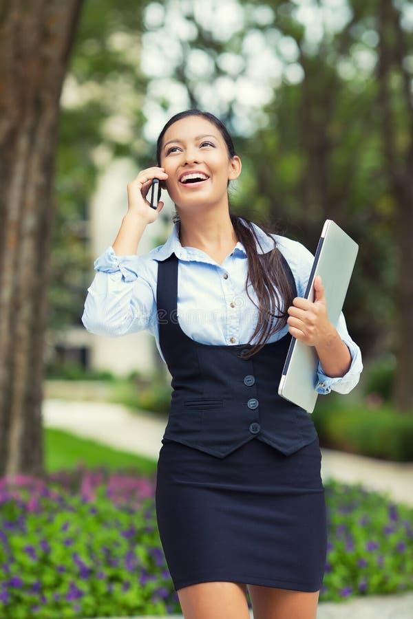 Mulher de negócio ocupada feliz que anda ao falar em um telefone esperto foto de stock royalty free