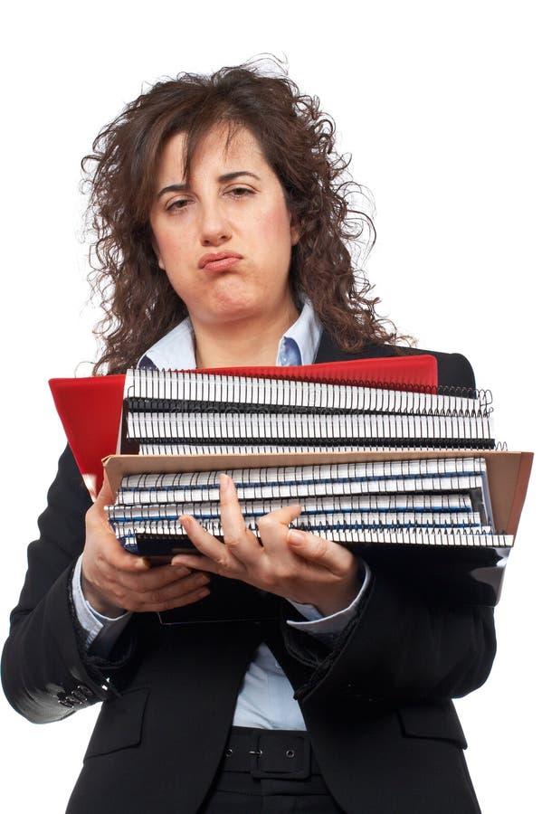 Mulher de negócio ocupada que carreg arquivos empilhados fotografia de stock