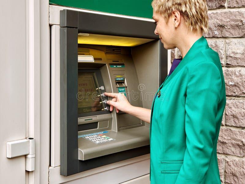 A mulher de negócio opera o ATM fotos de stock