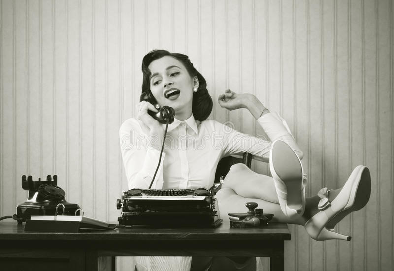 Mulher que fala no telefone na mesa fotografia de stock