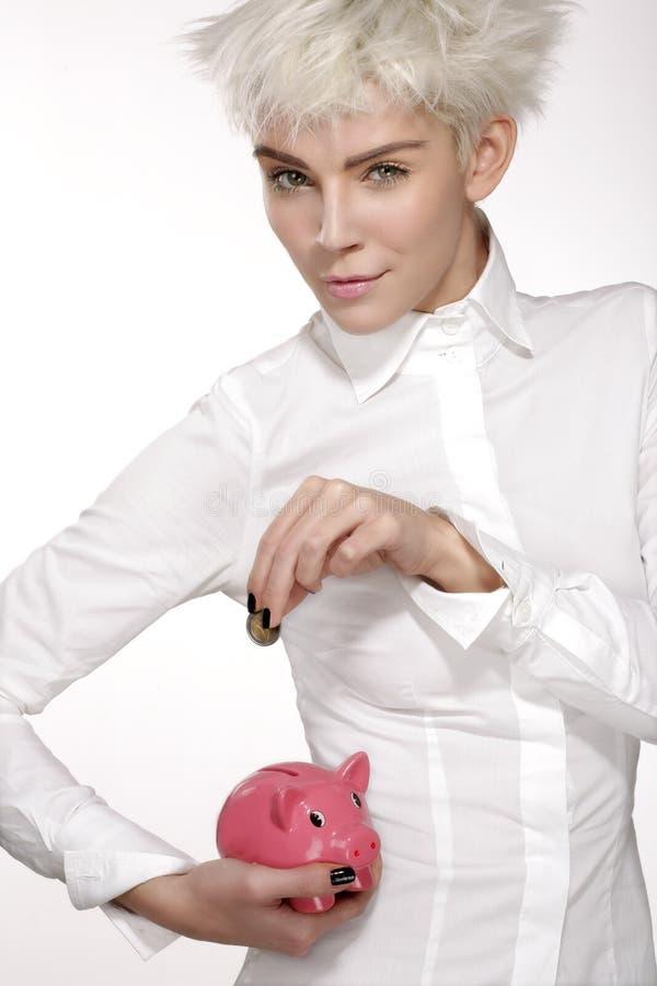 A mulher de negócio pôs uma moeda sobre um piggybank cor-de-rosa fotos de stock