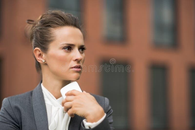 Mulher de negócio pensativa perto do smartphone de fala do prédio de escritórios fotos de stock royalty free