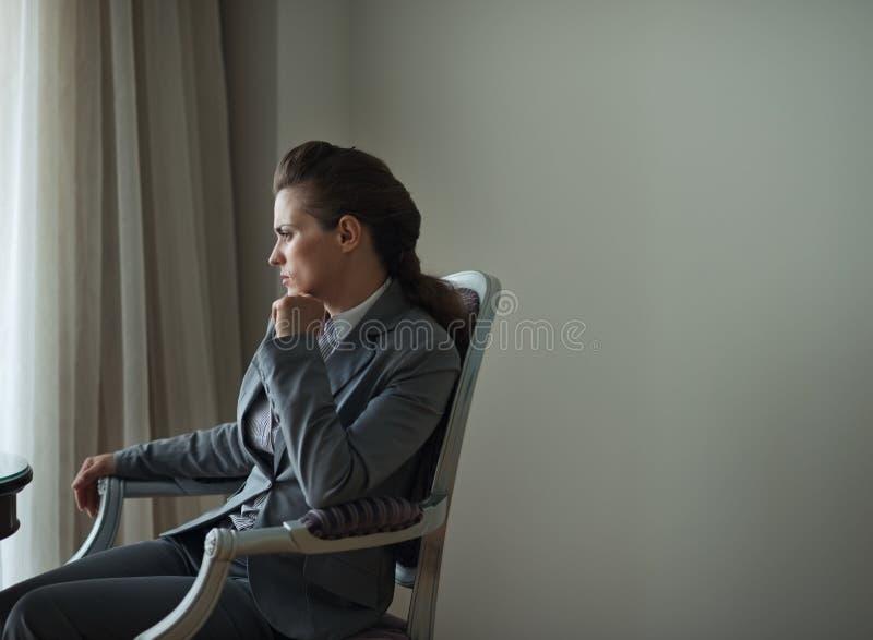 Mulher de negócio pensativa que senta-se no quarto de hotel foto de stock