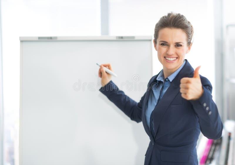 Mulher de negócio perto do flipchart que mostra os polegares acima foto de stock royalty free