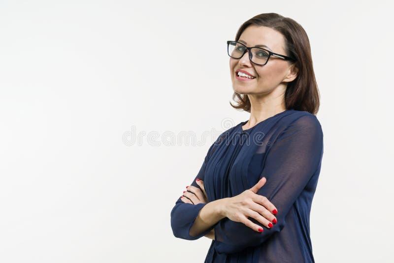 Mulher de negócio positiva da Idade Média que levanta sobre o branco com os braços cruzados fotos de stock royalty free