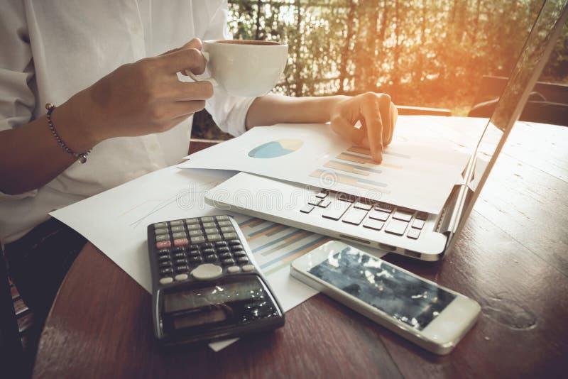 Mulher de negócio que analisa o original do gráfico com portátil e que guarda o tom do vintage do café foto de stock royalty free