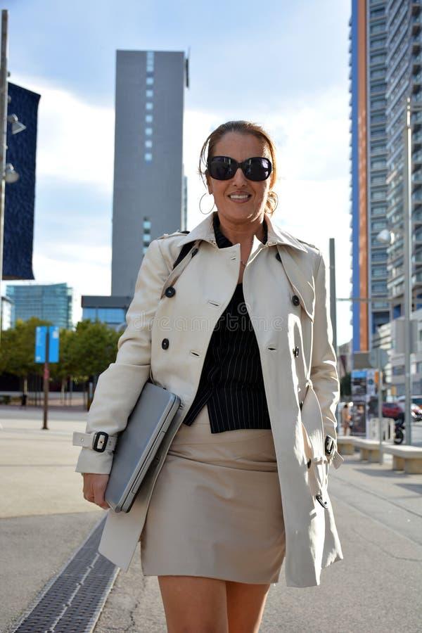 Mulher de negócio que anda abaixo da rua fotografia de stock