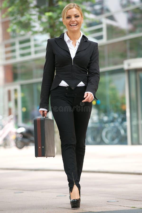 Mulher de negócio que anda na cidade com pasta imagem de stock