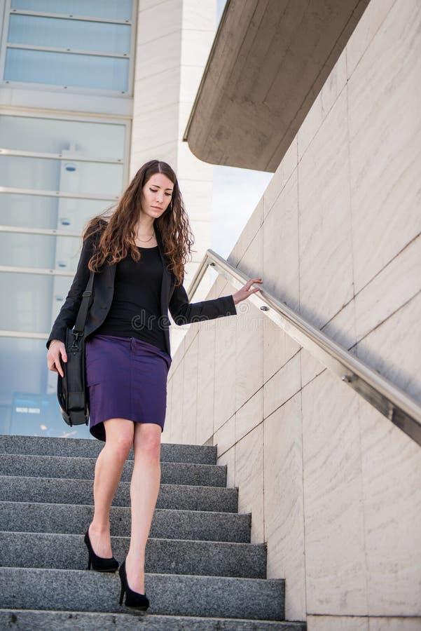 Mulher de negócio que anda na pressa em escadas imagens de stock