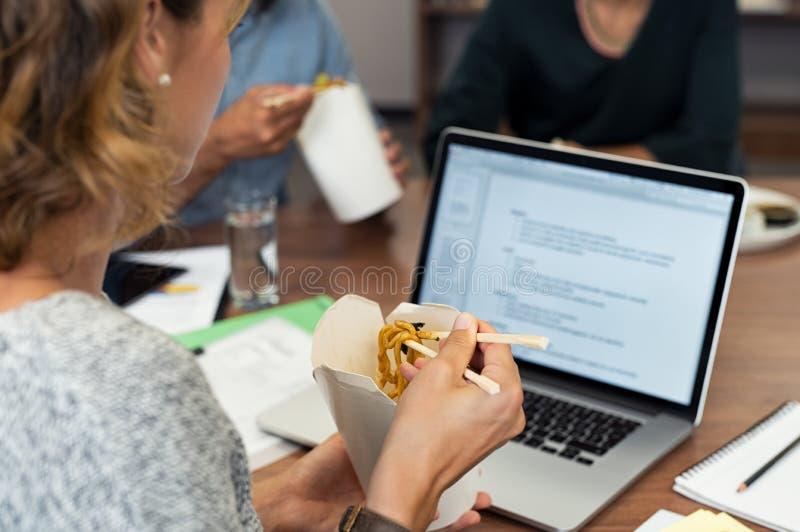 Mulher de negócio que come macarronetes ao trabalhar imagens de stock royalty free