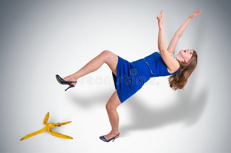 Mulher de negócio que desliza e que cai de uma casca da banana imagem de stock royalty free