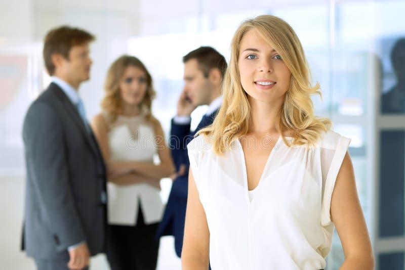 Mulher de negócio que está reta e que smilling no escritório imagem de stock