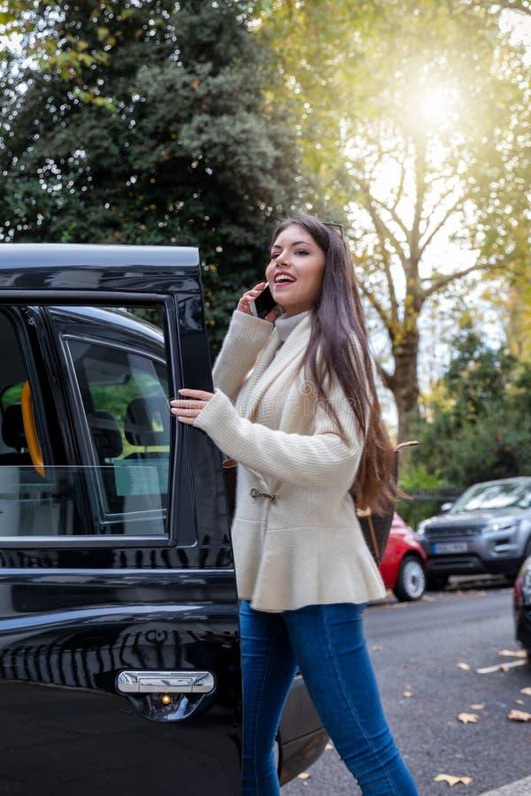 Mulher de negócio que fala em seu telefone celular enquanto etapas em um táxi preto imagens de stock royalty free