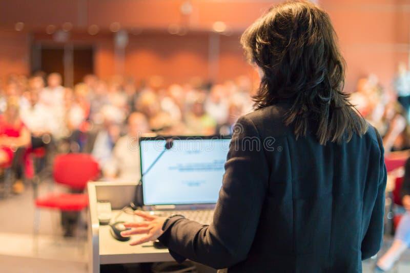 Mulher de negócio que fala na conferência