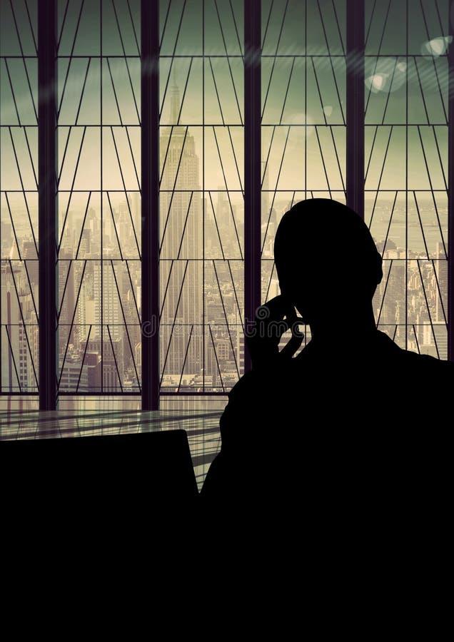 Mulher de negócio que fala na silhueta do telefone contra a construção fotografia de stock