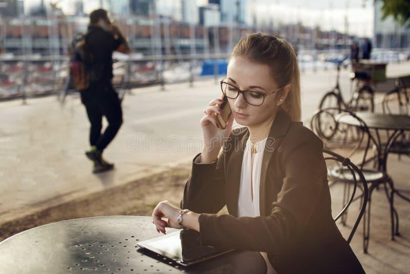 Mulher de negócio que fala no selfphone e que olha o relógio fotografia de stock