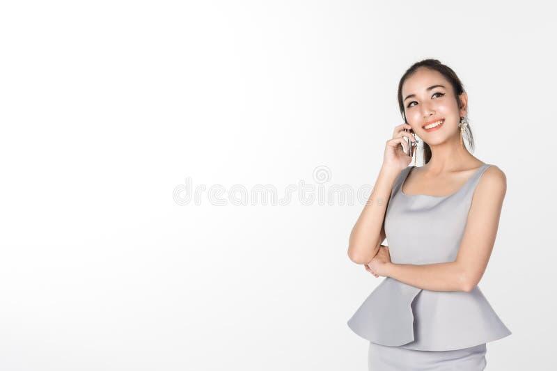 Mulher de negócio que fala no telefone celular e no sorriso isolados no fundo branco foto de stock