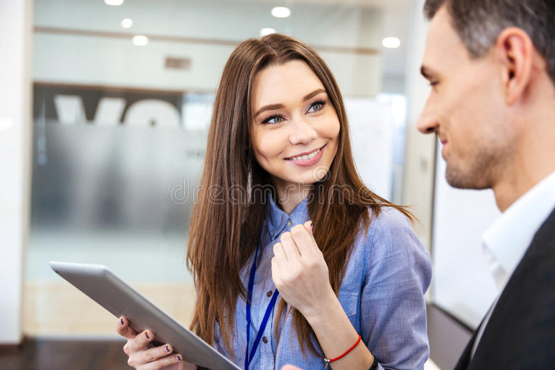 Mulher de negócio que fala a seu cliente e que usa a tabuleta imagens de stock