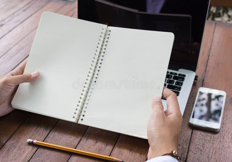 Mulher de negócio que guarda o caderno vazio com portátil e telefone celular fotografia de stock