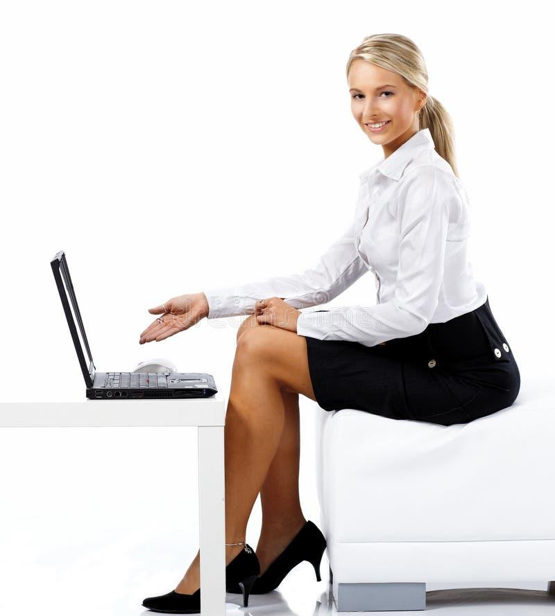 Mulher de negócio que indica um portátil fotos de stock