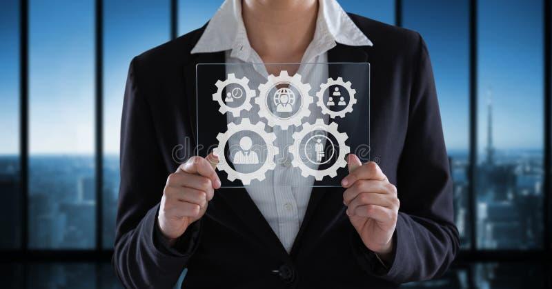 Mulher de negócio que interage com os povos em gráficos das rodas denteadas contra o fundo do escritório imagem de stock