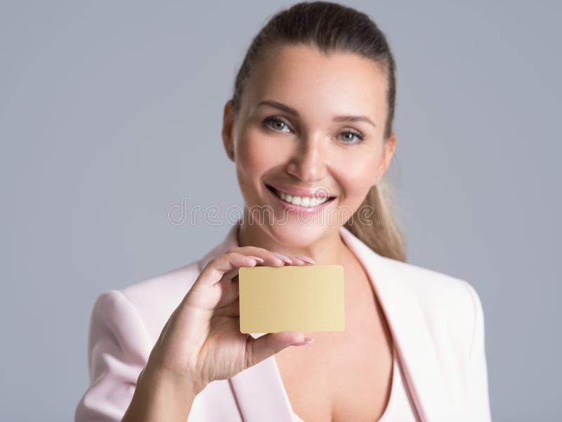 Mulher de negócio que mantém o cartão de crédito contra sua cara isolado imagem de stock royalty free