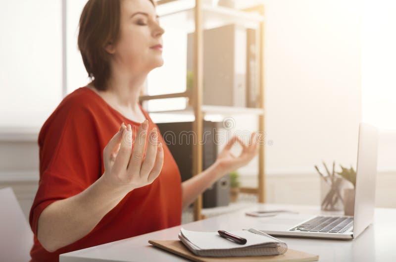 Mulher de negócio que medita perto do portátil foto de stock royalty free
